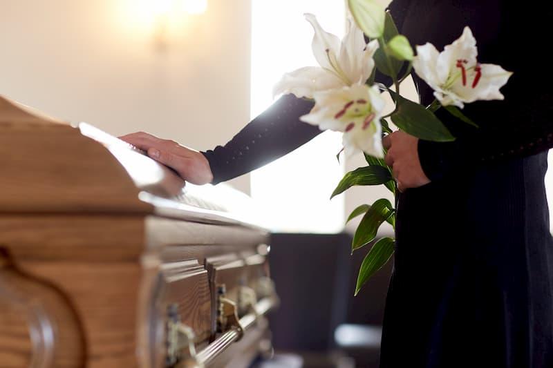 kobieta trzymająca białe kwiaty i opierająca się o trumnę