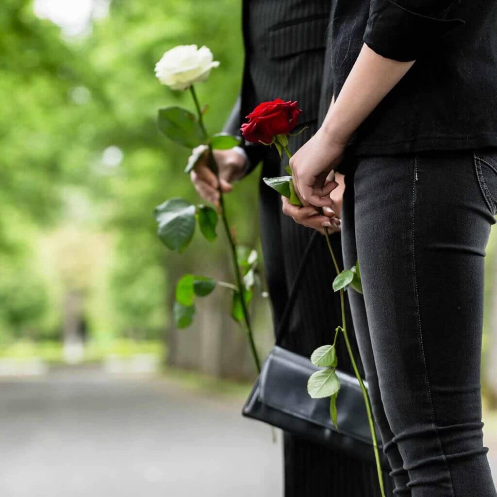 ludzie trzymający białą i czerwoną różę